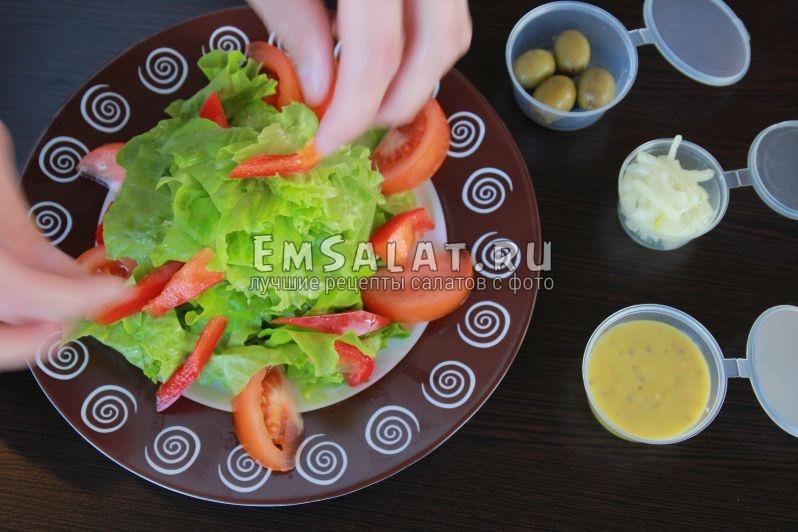 Дольки помидоров, перья сладкого перца, кольца маринованного лука на листьях салата