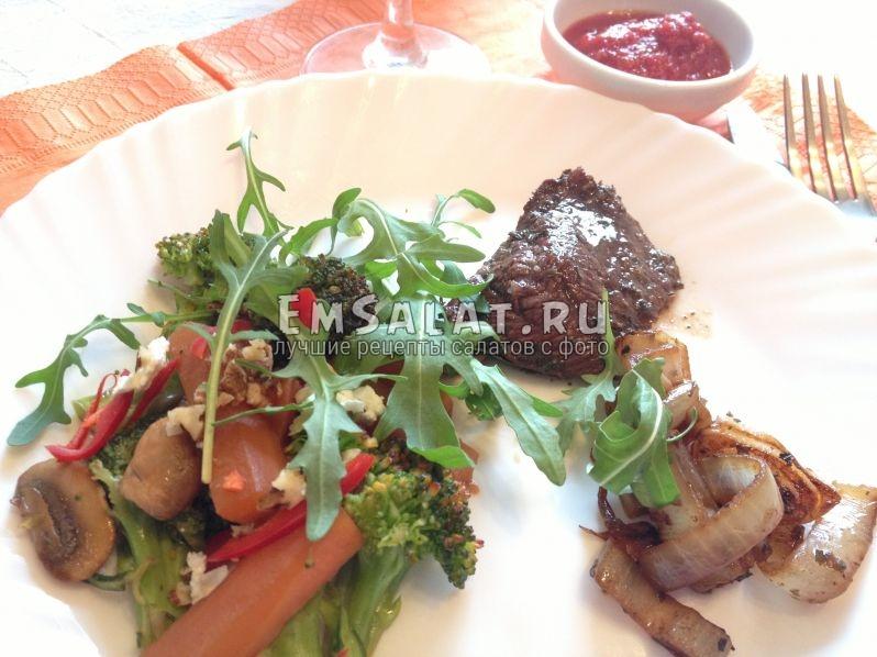 готовый салат в тарелке украшен рукколой и сыром