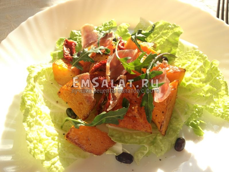 салат собран в тарелке, украшен рукколой и черной фасолью