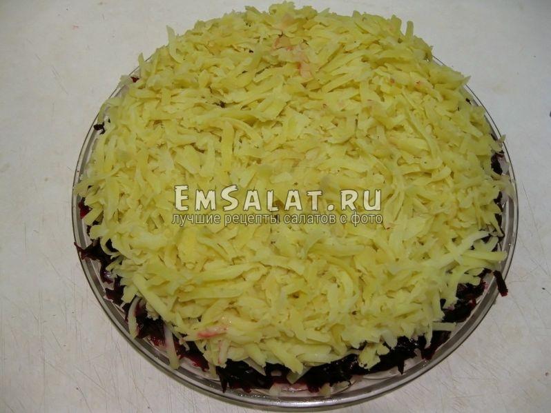 варенный и натертый картофель распределяем ровным слоем на салате Зимняя шуба