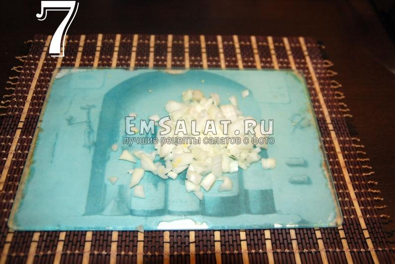 Измельченный лук для приготовления салата из соленой скумбрии в виде рулета.