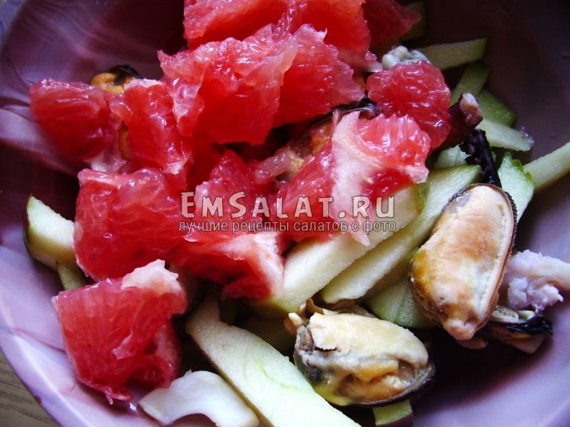 Кусочки грейпфрута добавлены в тарелку яблоку и морепродуктам
