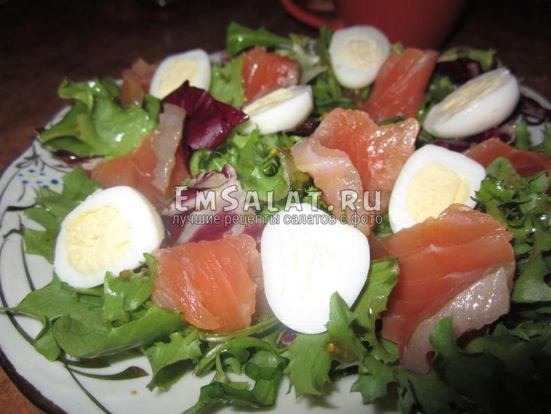 Выкладываем яйца и рыбу на листья салата