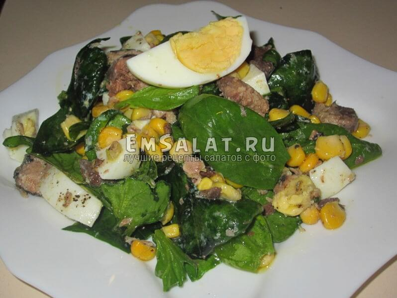 салат из шпината, кукурузы и тунца на тарелке, украшен яйцом