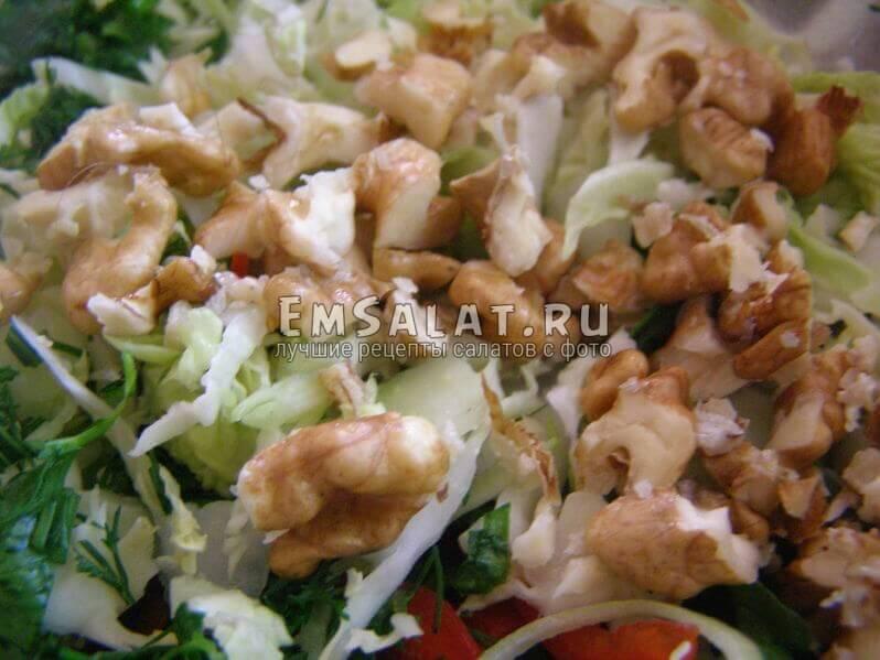орехи добавлены в миску, капуста савойская и зелень