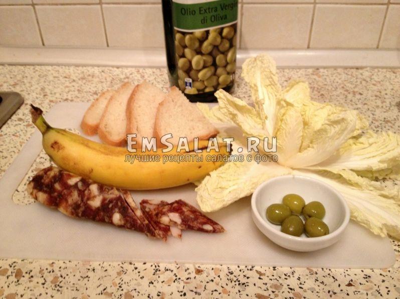 Продукты подготовлены для салата - пекинская капуста, банан, колбаса сырокопченая, белый хлеб, оливковое масло