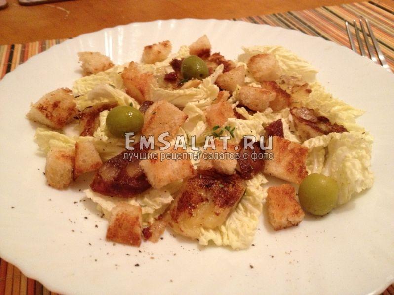 готовый салат в тарелке украшен оливками и веточкой тимьяна