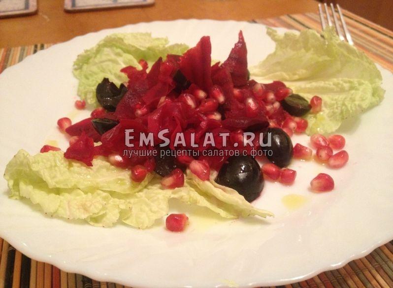 свекольный салат в тарелке украшен сладкими ягодами синего винограда