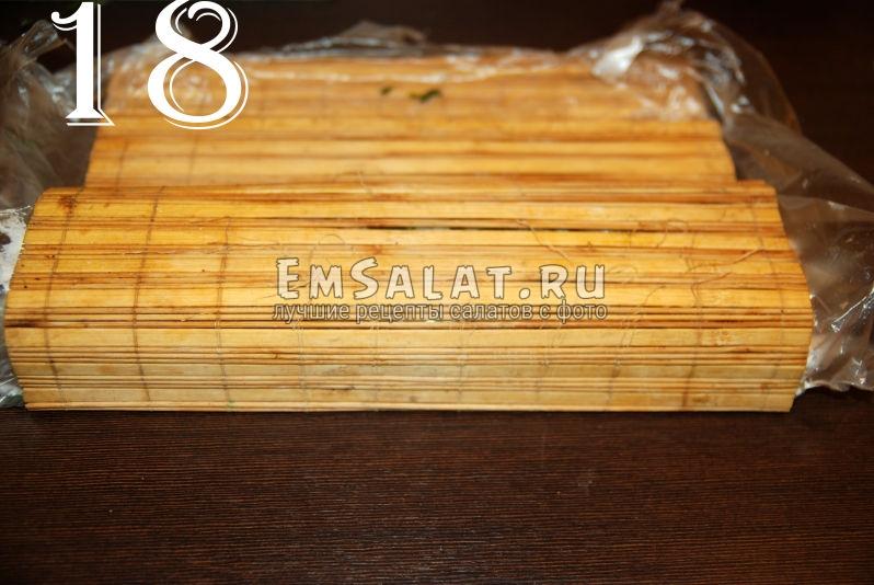 Скручиваем рулет из соленой салаки при помощи деревянного коврика.