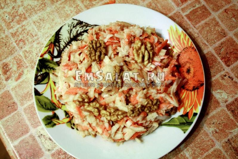 Салат из яблок и моркови, украшен орехами